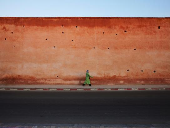 Woman walking along a clay wall