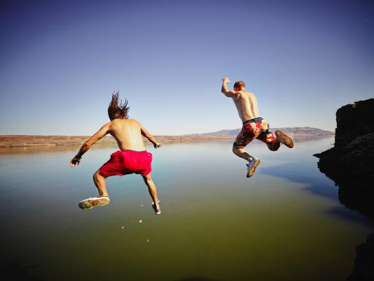 Two male friends jumping into river together