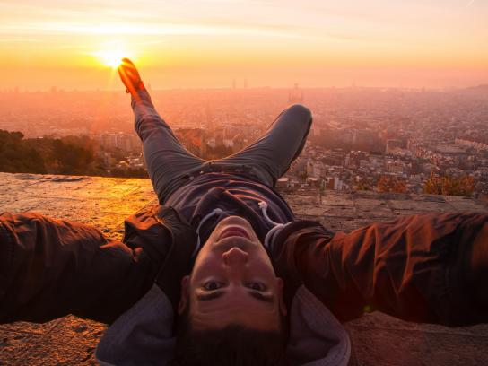 Guy taking a original selfie laying on the Barcelona bunkers (Turo de la Rovira) with the Barcelona cityscape on beautiful sunrise light
