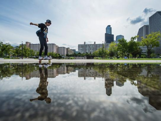 Skateboarding man reflected in water
