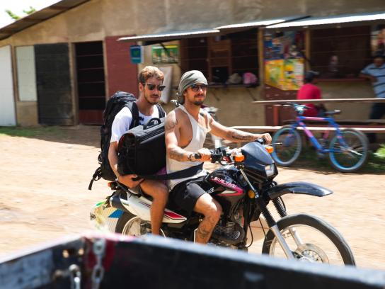 Two male friends ride a motorcycle